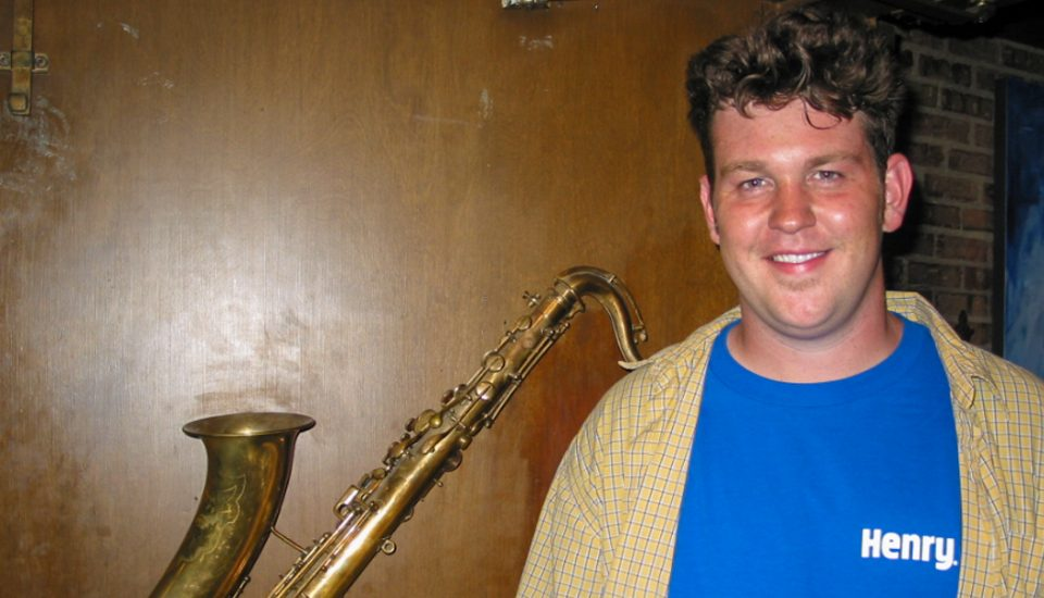 man standing in front of saxophone hanging on wall